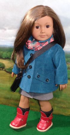 Sophisticated set for your favorite 18 inch doll! The slim-line long jacket, made from a teal blue soft cotton corduroy, is somewhat fitted, fully lined with a teal cotton print, has topstitching detail, straight collar, front pocket flaps, back half-belt, and closes in front with black buttons. The outfit under the jacket consists of a slim skirt with faux-front buttons, made from a stretch gray cotton with elastic in casing at the waist. The blouse and scarf are made from a recycled scarf…