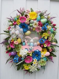 I adore the pops of vibrant blue in this floral Easter wreath. #wreath #Easter #decor #decorations #bunny #eggs #cute #spring #flowers