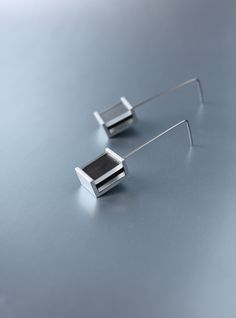 hladina Autorské náušnice. Ručně broušený eloxovaný hliník (ochranná úprava povrchu, nečerná, lehký na nošení) v geometrické kompozici s průhledným plastem a černou mikropryží. Háček z nealergického osteofixu - chirurgická ocel, kovová zarážka. Celková délka 5 cm. Samotný kovový díl má rozměr 1,5 cm na výšku, 1 cm na šířku, 0,8 cm na hloubku. Možnost ...