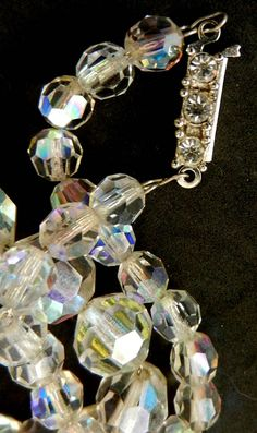 Harder to find is this Authentic 1940 1 strand necklace, beautiful Austrian crystals with warm boreal light, that is strung on a silver tone chain. The beads start out smaller by the silvertone rectangle box-clasp and work up to larger beads It ranges from 6mm to 13mm The beads fire off a large variety of colors in the light and sparkle in the lowest of light. The necklace has a great quality crystals and rich feel to it. The beads have a light AB finish to them and the lovely small clasp is…