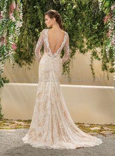 Modified A-line wedding dress with a low back and sleeves. Ivory lace over a nude slip is romantic and a little bohemian or vintage in style. This sample gown can be found at Le Dress Boutique for under $900.