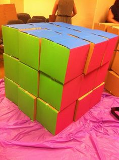 80's party Giant Rubix cube out of 12x12 cardboard boxes and acrylic paint.  Fun party game idea!: