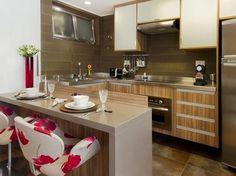 A cozinha americana se integra à sala e o balcão conta com duas cadeiras confortáveis.