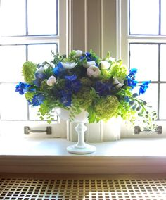 www.sweetpfloral.com Milk glass compote blue and green spring centerpiece. Asymmetry with ranunculus, anemone, viburnum, maidenhair fern, delphinium and jade dendrobium orchids for u of m wedding at the Michigan League