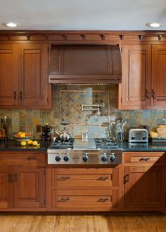 Range wall in Crown Point kitchen that combines Prairie and Arts & Crafts styling. #Craftsman #rangehood