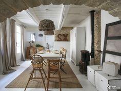 Salle à manger dans une maison de l'Uzège, table et chaises de jardin 'AM.PM.', chaises hautes en bois et tapis en coco 'Ikea'