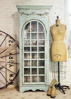 A faded mint green cabinet next to a dress form- perfect vintage inspired decor!