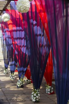 Pleated tent holders with bunch of carnations at the base for a nautical themed wedding decoration.| weddingz.in | India's Largest Wedding Company | Indian Wedding Decoration Inspiration |