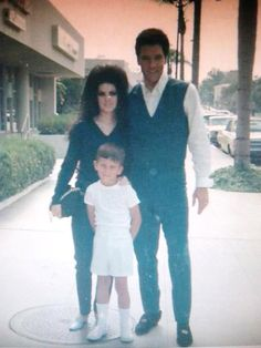 Elvis and Priscilla stop for a photograph picture with a young fan, c. 1967.