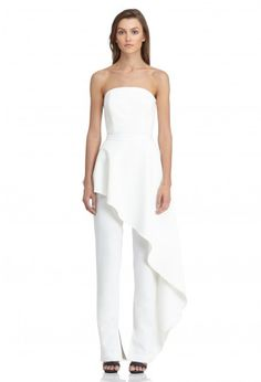 White strapless jumpsuit with feature asymmetric peplum.   Fitted waist with ruffled peplum in self-fabric attached along the leg seam.  The Adelia straight leg jumpsuit has a concealed centre zip back fastening.   Splits in the trousers to the inside ankle give this classic jumpsuit a modern update.   From the Winter 16 Collection.