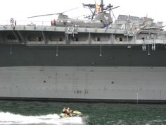 Couple on jet ski passes the USS Midway Aircraft Museum with people on flight deck, San Diego, California | Photo by Patty Mooney of Crystal Pyramid Productions in San Diego, California - sandiegovideoproduction.com
