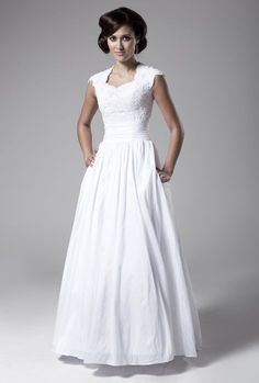 A simple, modest wedding gown with Queen Anne neckline, lace bodice embellished with beading and sequins, modified cap sleeves, rouched natural waist, taffeta ball gown skirt, and hidden side pockets. by Elyse Hagen
