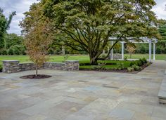 This bluestone patio is dry laid. The color is full range as you can see the different shades. A beautiful seat wall was included along with a shade tree set in the patio.