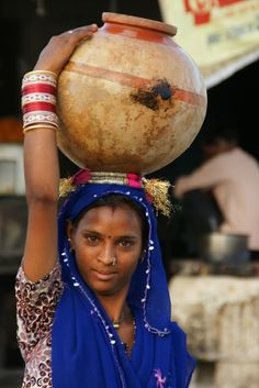 A woman with a very large pot of water on her head.   Near Jaipur, India