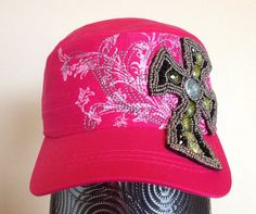 This hot pink cadet cap features a white screen printed pattern across the front of the hat, along with grey embroidery that follows the pattern. There is a black fabric cross embellished with metallic and green patterned beading that covers part of the front and bill of the cap.  - Three-panel construction. - Embroidered design. - Screen printed design. - Patterned and metallic beads. - Adjustable closure at back. - 100% Cotton.