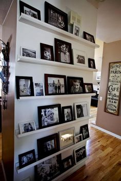 A wall for pictures in frames using small shelves - love this idea