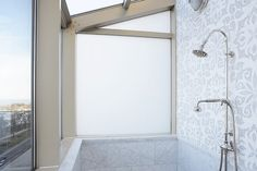 High-rise bathroom with rain shower head, marble tiles paired with mosaic tile shower surround with shower skylight.
