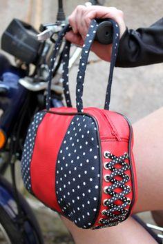 Kabelka z červené koženky v kombinaci s puntíkatou látkou, na boku kabelky ozdobná šněrovačka.