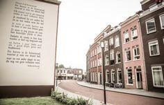 Mijn gedicht. Ik woonde daar.  Muurgedicht 'Huizen in de Binnenstad'  Het eerste Almelose muurgedicht op de muur van het appartementengebouw Manchester aan de Holtjesstraat in de zuidelijke binnenstad.  Het gedicht 'huizen in de binnenstad' van Willem Wilmink werd op de muur geschilderd door de Almelose kunstenaar Freddy Hoevers.  Muurgedichten dragen bij aan het beleven van poëzie door de toevallige voorbijganger. Het heeft een element van verrassing.