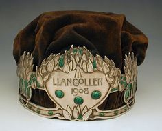 A crown made in arts & crafts/art nouveau style that was given to the winner of the free verse competition at the National Eisteddfod of Wales. Made of silver, green enamel and velvet.  Produced in 1908 by Philip & Thomas Vaughton.Source
