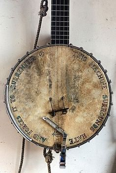 """Pete Seeger's banjo; this banjo has been many places and brightened the lives of many.  Can you read the words? It says, """"This machine surrounds hate and forces it surrender."""""""