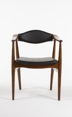 The Ox chair is sculpted from solid ash hardwood with a walnut finish. The padded, elliptical backrest and seat are covered with smooth, black polyurethane. An extension of the arm rest to the back pr