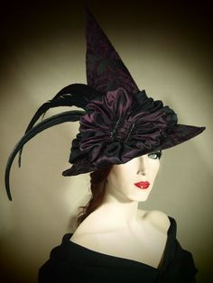 This hat is one of my personal favorites!!! So elegant!     The base of this hat is made of a black and plum chenille Jacquard fabric and is adorned with a two tone plum taffeta swag. To top it all off is a black rhinestone buckle and long black feathers! This hat is sure to fulfill you purple passion! This hat is fully lined and (like all of my hats) is one of a kind, and signed, dated and named. This ones name is Plum Gorgeous. It measures 21 and is a Short Sport style. If you would like…