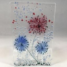 This is a clear glass plaque (approximately 10cm x 6cm) featuring flowers in shades of blue and pink. The plaque looks amazing used as decor both in daylight and at night with a candle in the attached tea light holder. This will make a great gift for someone special or as a treat for