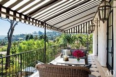 On the newly built living room terrace at the Los Angeles home of Ellen Pompeo, Gloster wicker seats with Schumacher upholstery are shaded by a Sunbrella-fabric awning. The home was renovated by designer Martyn Lawrence Bullard | archdigest.com