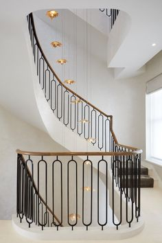 The floating, sculptural quality of the chandelier makes an eye-catching statement, and complements the muted backdrop of polished plaster walls, wrought iron balustrade and oak handrail. Staircase Railing Design, Interior Stair Railing, Modern Stair Railing, Staircase Handrail, Balcony Railing Design, House Staircase, Iron Stair Railing, Home Stairs Design, Modern Stairs