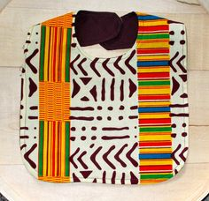 This baby bib features an African Kente print fabric.  It measures 7 inches long from neck to bottom and 9 inches wide with a Velcro neck closure.  Fabric is 100% cotton and has been pre-washed. Machine wash in cold water, tumble dry low, warm iron, DO NOT USE BLEACH