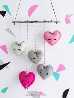 DIY Felt Heart Mobile - sweet idea for a Valentine's Day craft! Complete tutorial shows hot to make the padded stitched hearts out of felt and turn them into a cute mobile. Project includes a free downloadable template. Fun to make with kids!