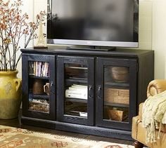 Set up our bedroom television like this. This Printer's TV Stand/Glass Cabinet from Pottery Barn. Re-create the look with Expedit from IKEA.
