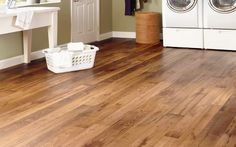 If you have hardwood flooring throughout your home, consider extending that look to your laundry room with a vinyl floor that looks like hardwood. A wood-look vinyl floor, with the colors and graining you'd expect to find in hardwood, provides a warm and comfortable surface to stand on while sorting clothes. Vinyl flooring is also a good choice for a laundry room since this room is likely to experience higher degrees of humidity and occasional spills and splashes.