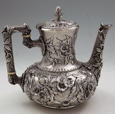 A finely chased antique demitasse pot by Dominick and Haff of New York. Naturalistic handle with three dimensional work. The lid hinges back to open. High relief chasing of flowers and leaves against a stippled background. Circa 1882