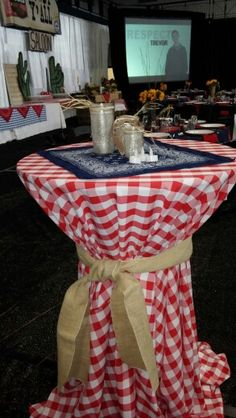 Cocktail tables were covered in red check table cloths tied with burlap Sashes. Center was a blue bandanna with three different sized mason jars painted with glitter on inside and tied with Raffia. Used battery powered votives to light. Rusty horse shoes were propped in the middle of jars