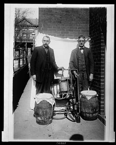 Two men posing with a whiskey still