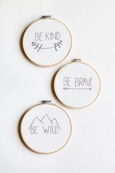 """DESCRIPTION Three small wooden hoops with hand embroidered designs that read """"Be Kind,"""" """"Be Brave,"""" and """"Be Wild"""" in gray. Hand stitched by women in the Ukraine"""