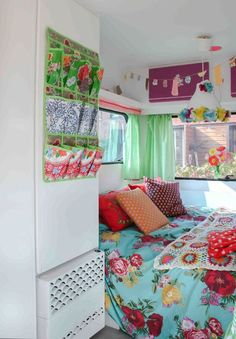 I am in love with this kitsch caravan makeover that I found via caravanity . The cross stitch painted wall art reminds me of my old logo. The kitsch textiles and plastic baskets are so sweet!