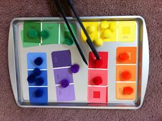 Busy Bag / Tot Tray Idea for Toddler, using cookie sheet, salad tongs, colored pom-poms, and paint chip strips