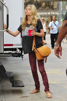 """Clemence Poesy looking dressed down in burgundy tie dye jeans and a loose t-shirt on the set of """"Gossip Girl"""" at the Empire Hotel on the Upper West Side in New York City."""