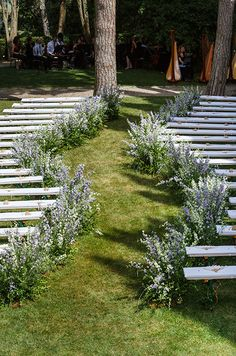 A custom serpentine wedding aisle lined with wild lavender leads to a full orchestra at the far end of the garden.