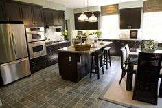 Open living space dark kitchen design with eat-in kitchen bar and separate dining area.