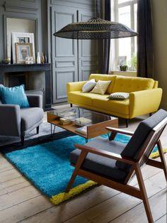 Un canapé jaune dans un appartement style haussmannien