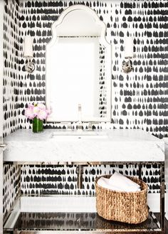 Wallpapered powder room with curved mirror