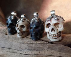 This listing is for four amazing Tibetan hand-carved skull pendants (sold individually; price is for ONE skull pendant). The two dark skulls are carved horn and the two light-colored skulls are carved bone. The tops of all four are adorned with a highly detailed repousse cap consisting of a curly leaf and vine motif culminating in a perfect single lotus blossom on the back. The large bail has a wide opening that will accommodate many stringing possibilities, including thick leather, multiple…