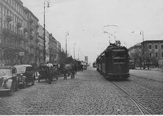"""Na brukowanej ulicy widoczny tramwaj typu H linii """"24"""" nr boczny 373, samochody i wozy konne."""