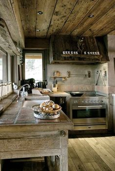 weathered terracotta tiled countertop with unfinished wooden base and concrete walls with terracotta tile sidesplash and salvaged wood shelf above sink rustic wood range hood surround