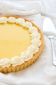Classic lemon tart with a lemon curd filling in a buttery tart shell with a hint of coconut. | tamingofthespoon.com