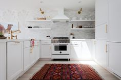 Wall of tile | white stove & hood | brass handles | combination of cabinets & shelving